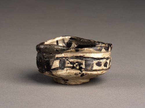 重要文化財公開「元屋敷陶器窯跡出土品展」(第1展示室) 「ウス茶ノ時ハ セト茶碗 ヒツミ候也 ヘウケモノ也」(「宗湛日記」慶長4(1599)年2月28日)。織部茶碗の描写として知られる有名な一節です。土岐市では、織部焼の文献上の初見とされるこの日記が記された2月28日を「織部の日」と制定しています。本展は、第31回織部の日記念事業として、重要文化財・元屋敷陶器窯跡出土品を公開するものです。 国史跡「元屋敷陶器窯跡」は土岐市泉町久尻に所在する古窯跡群で、安土桃山時代から江戸時代初頭に大流行した「茶の湯」の影響を受け、瀬戸黒、黄瀬戸、志野、織部といった茶陶「美濃桃山陶」が生産されました。歪んだ形状と華やかな色彩を特徴とする美濃桃山陶ですが、その変化は瀬戸黒と黄瀬戸に始まり、志野、織部へと進むにつれ顕著になっていき、織部の沓茶碗や色彩豊かな向付はその到達点といえます。 今年度は、第2展示室において企画展「山茶碗」を同時開催します。山茶碗は、平安時代末から室町時代にかけて作られたやきもので、庶民向けの雑器としてとくに碗と皿が大量生産されました。無釉で土味そのままの「山茶碗」は素朴な味わいを見せ、同じ美濃窯で作られたやきものながら、極端なまでに作為が加えられた「織部茶碗」とは対極にあります。そして、その用途も日用食器と茶陶という、まったく異なるものです。本展では、山茶碗と比較していただくことも意図し、元屋敷の出土品により織部の沓茶碗に至るまでの茶碗の変遷をご紹介します。また、茶室で使用される水指や茶入、懐石用食器としての向付や大鉢など、茶の湯の道具という視点で、重要文化財をご鑑賞いただきたいと考えています。 黒織部(重要文化財) 黒織部(重要文化財)